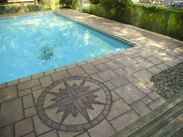 A compass rose is placed in the stamped concrete pool deck providing just the right element of design.