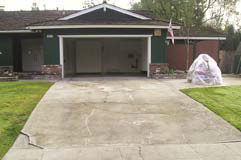 A drab concrete driveway that is in desperate need of a decorative concrete makeover.