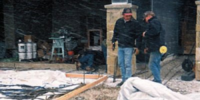Men on a concrete construction job site, snow flying through the air, contemplating their decorative concrete stamping job ahead.