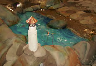 A depiction of a lighthouse near a concrete fountain.
