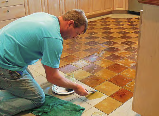 A man puts down concrete stain on a floor with a geometric pattern.