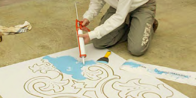 Applying a stencil to a floor creating an artistic look when artistic talent is lacking.