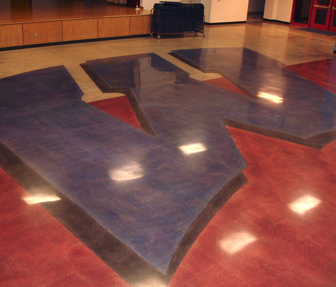 A school logo is placed on the floor with colors and polished concrete.