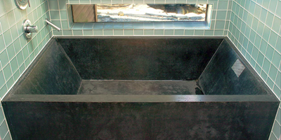 Concrete tub that was custom made for this space using black concrete.