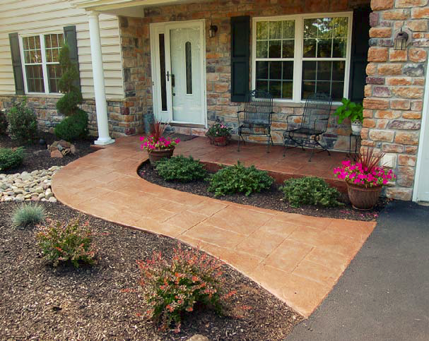 A stained and stamped concrete pathway leading to a front door.