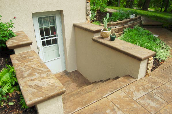 Steps down to a basement outdoors that have been refinished with stamped concrete.
