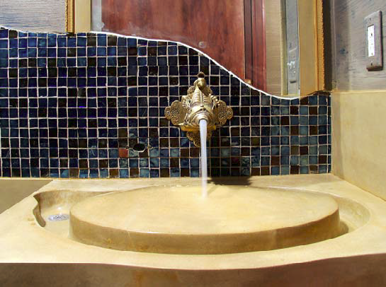 Unique concrete sink that also acts as a water feature in a bathroom.