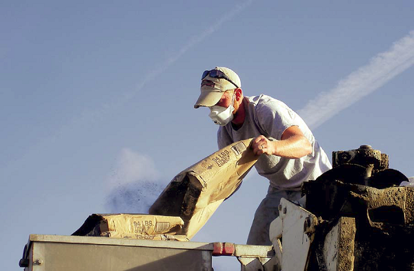 Particulate matter can be extremely harmful when inhaled. This picture shows a man dumping concrete mix into a hopper while wearing a dust mask.