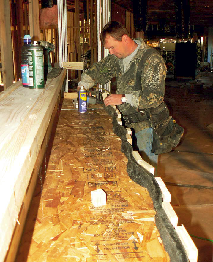 Winkler carefully pins a FossilCrete form to give this countertop a natural-looking edge.