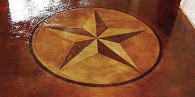 A star stenciled onto concrete in earth tone stains.