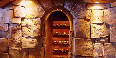 Vertical carved concrete acts as an entry to a wine cellar.