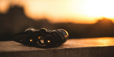A set of binoculars rests on a ledge at sunset.