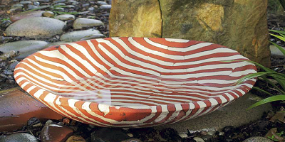 Striped red and white concrete bowl in nature.