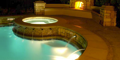 Concrete pool deck with lighted swimming pool.