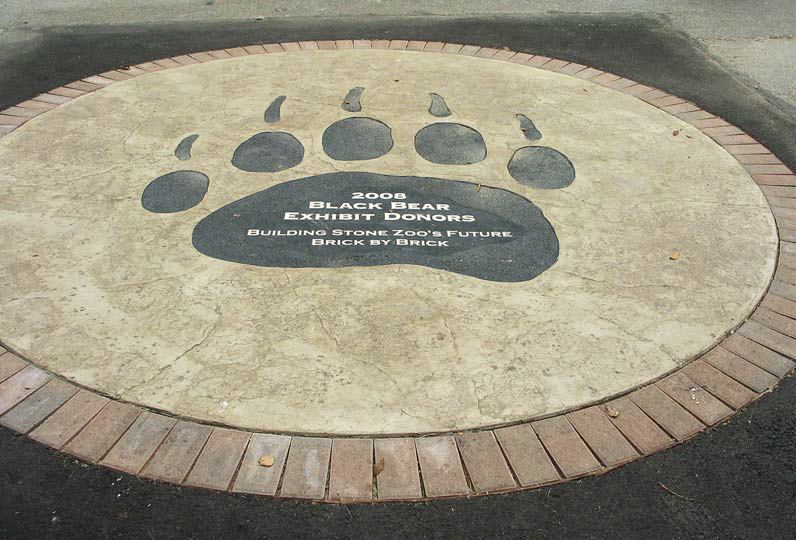 Large stamped concrete circle with a logo in the center of a bear paw.