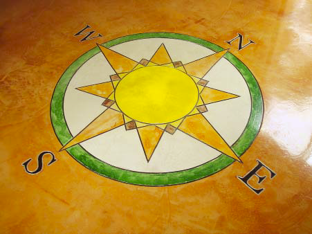 Compass rose colored on a floor in greens and yellows.