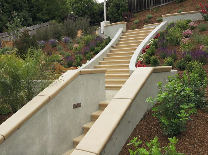 Stairs lead the homeowners on this three tiered concrete patio.