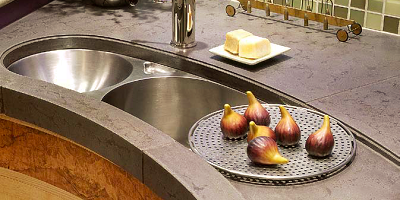 Countertop design with a built in sink and figs sitting on the drainboard.