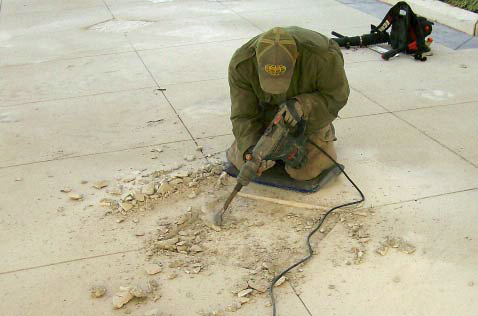 Using a vibrating hammer to break up old concrete.