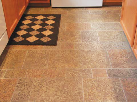 Overlay treatment in this kitchen with reds and browns and gray grout-like lines.