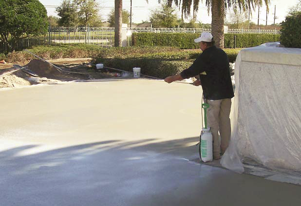 Using a sprayer on concrete.