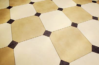 Checkerboard concrete tiles with alternating colors of yellow and white with brown inserts.
