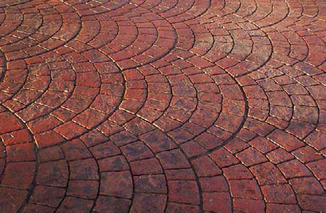 Radial stamped concrete colored with a brick red.