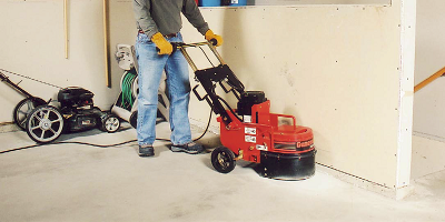 A man running a surface prep machine to get his floor ready for a concrete application