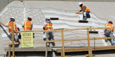 TB Penick construction workers placing an American Flag made of Terrazzo on a slanted concrete surface.
