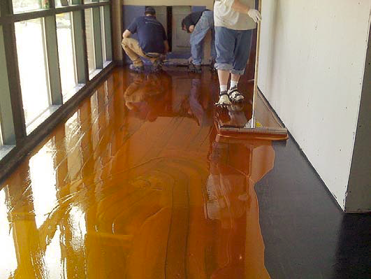 Pushing the stain along the concrete floor with a broom is an easy way to apply the concrete stain.