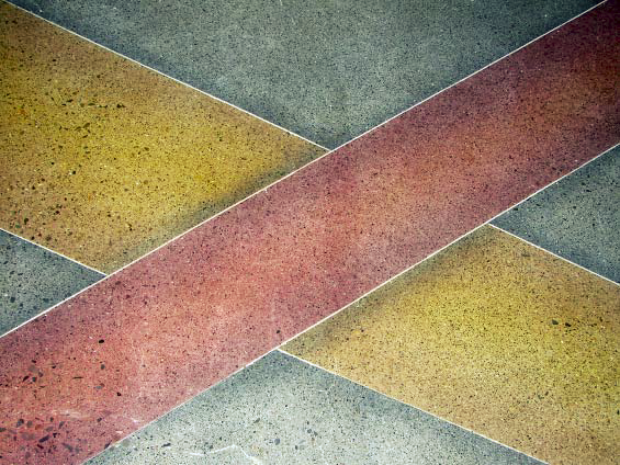 Using dyes on polished concrete these yellow and red ribbons intersect on each other on this concrete floor.