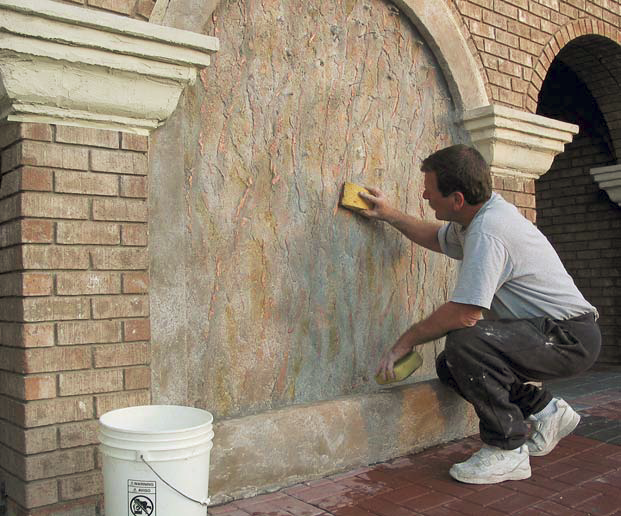 Man applying color to a wall that will feature a waterfall.
