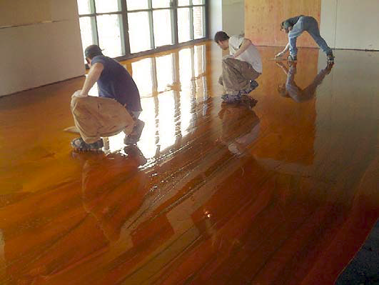 Three contractors working on a stain installation.
