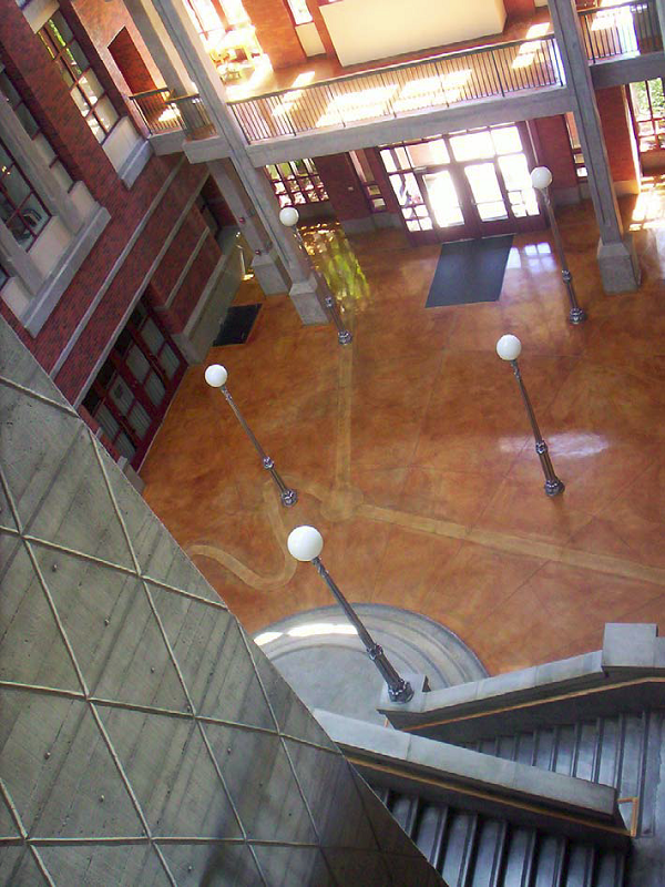 Deschutes Hall at the University of Oregon in Eugene. Note layers of detail in the natural-gray concrete elements — tie holes, board-formed butt joints, rustication strips — all supported by the warm, iron-salt-stained concrete slab. The variegated patina of the slab also includes layers of detail.