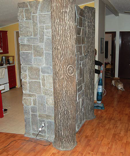 Indoor carved concrete log beam with carved concrete rock surround.