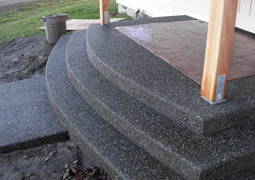 Exposed aggregate steps with stained concrete inlay under cover.