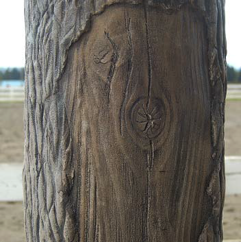 Verticaly carved concrete shaped into a log with missing bark pieces.