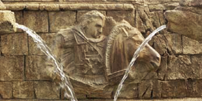 Relief design in the side of a roman aqueduct shows a horse and a roman soldier.