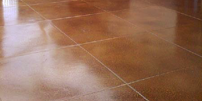 Stained concrete floor in a reddish brown with lighter grout lines.