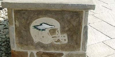 Outdoor concrete kitchen with a football helmet stamped in concrete on the side.
