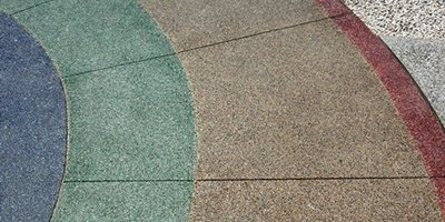 Stained concrete patio that shows blues, greens and reds in a circular pattern.