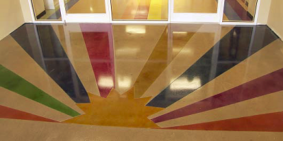 A sun with rays in rainbow colors has been dyed into this concete floor.
