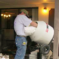 A man pours a bag mix for concrete countertops into a mixer before starting to form his countertops.