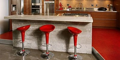 Industrial gray concrete bar top that is paired with three red bar style seats.