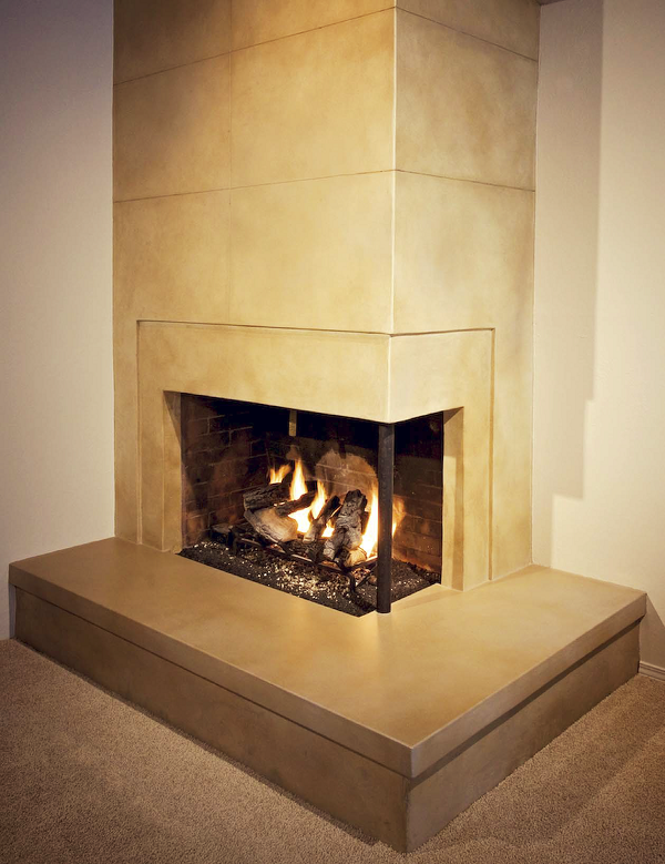 To create the look of this fireplace, Cement Elegance veneered the drywall above and around the fireplace façade with a cementitious microtopping, then cut a score pattern into it to simulate large tiles. The rest of the fireplace was all red brick, over which they installed a microtopping.