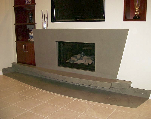 "Mike Wellman of Concast Studios worked with the client on the design of this fireplace, which matches the art deco style of the house. It has what he calls ""flowing rivers of decorative stone and shell."""