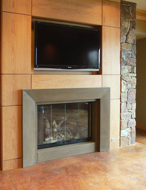 This single-piece GFRC fireplace from Absolute ConcreteWorks LLC was surround-cast in a solid color. The face tapers slightly towards the firebox. The block hearth is a separate piece.