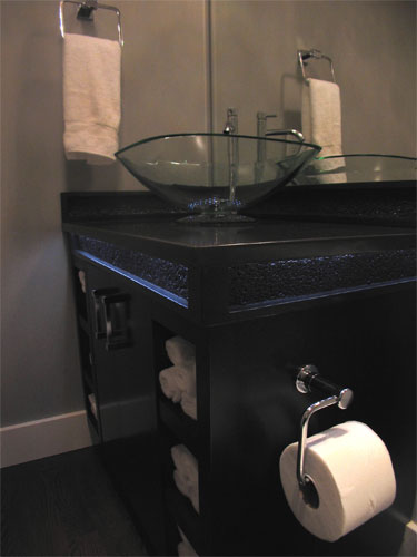 A roll of toilet paper attached to the side of this concrete vanity with a glass bowl sink.