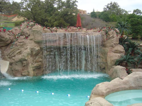 An enormous water fall was created in this backyard that flows over hand carved rocks and crashes into a bright blue pool below.