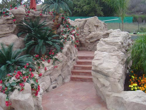 Landscaping and rock features work seamlessly together to create a concrete oasis in this backyard including steps built in to take guest to the next level of terrain.